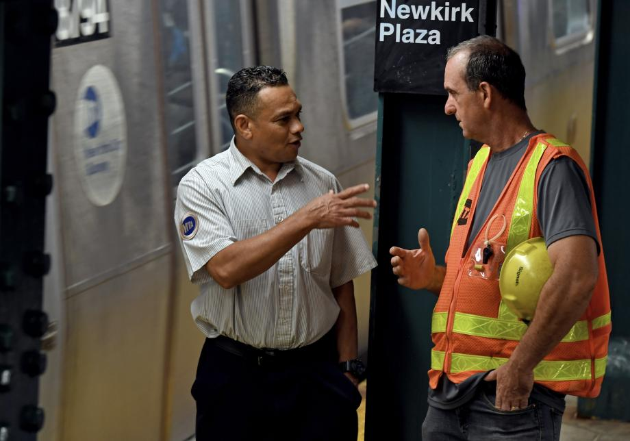 Two MTA employees, one in a short-sleeved collared shirt and the other in an orange construction vest and a hard hat, talk on a subway platform. A train is visible behind them.