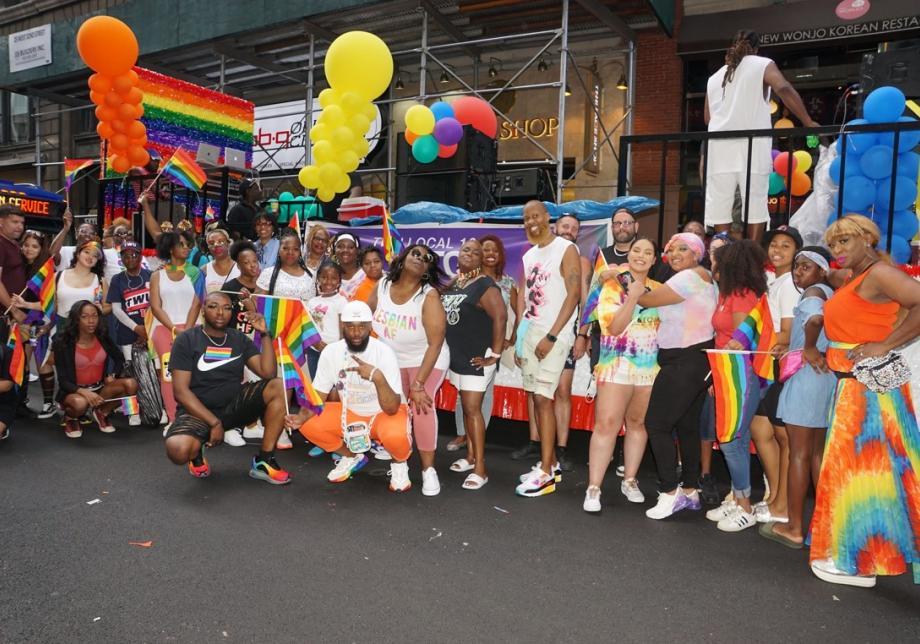 A big group of people, many wearing rainbow colors and carrying rainbow flags, smiles at the camera at a Pride Parade.