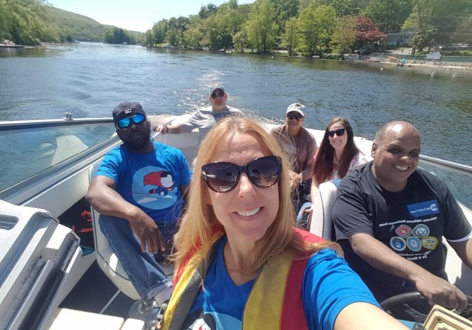 A woman in sunglasses takes a photo of herself and five other people in a boat on the water. Everyone is smiling, and one man is wearing a T-shirt that says Veterans Transit Employee Group.
