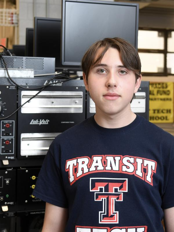 A young man wearing a Transit Tech shirt looks at the camera. Industrial equipment is visible behind him.
