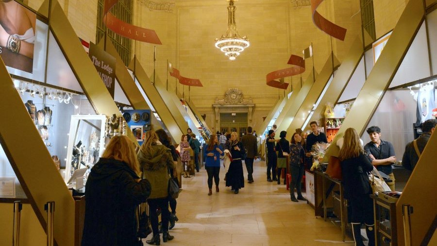 A photo of a market inside grand central terminal. Vendor booths stretch down both sides of a long aisle. Each one has small groups of people in front of it. A blond woman walks away from the camera.