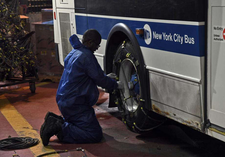 "A person kneels to put snow chains on the rear tire of a bus. The words ""New York City Bus"" are visible on the side of the vehicle."
