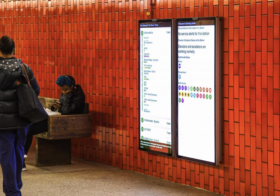 People sit near and walk by two large digital screens on the wall of a subway station. The screens show arriving trains and service status.